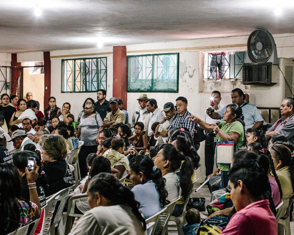 Towns people gather with law enforcement officials during a town hall at the San Gerardo church to air their concern that the government has not done enough to find their missing.