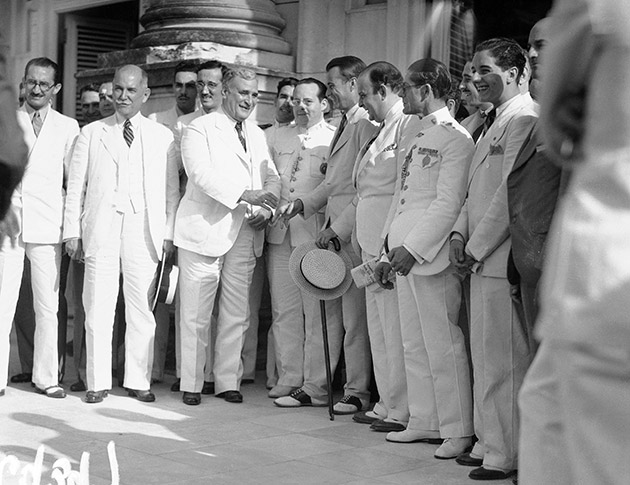 President Carlos Mendieta of Cuba, in white linen, exchanges greetings with U.S. Ambassador Jefferson Caffery in Havana upon hearing of the signing of the Cuban-American Treaty in Washington, May 31, 1934.
