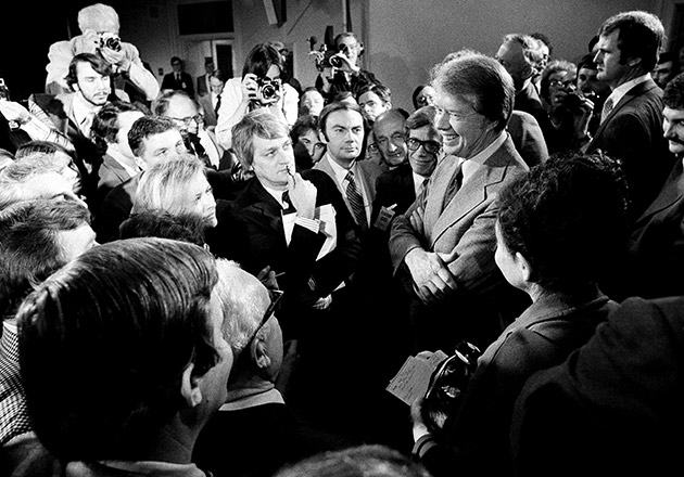 Pres. Jimmy Carter, right, is surrounded by reporters and photographers at the conclusion of his news conference in the Executive Office Building, Wednesday, March 9, 1977, Washington, D.C. He announced that the administration is lifting the ban on travel by U.N. citizens to Vietnam, North Korea, Cambodia and Cuba effective March 18.