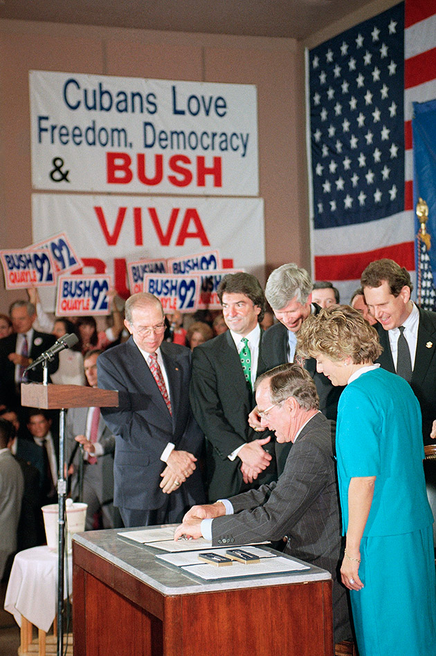 "U.S. President George H. Bush signs legislation in Miami, Friday, Oct. 23, 1992 that will tighten the embargo on Cuba. The President is surrounded by supporters in Miami as he signed the bill that he said would ""speed the inevitable demise of the Cuban Castro dictatorship."" President Bush made an ""Ask George Bush"" television question and answer appearance following the ceremony at a local TV station."
