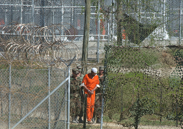 FILE - In this March 1, 2002 file photo, a detainee is escorted to interrogation by U.S. military guards at Camp X-Ray at Guantanamo Bay U.S. Naval Base, Cuba.