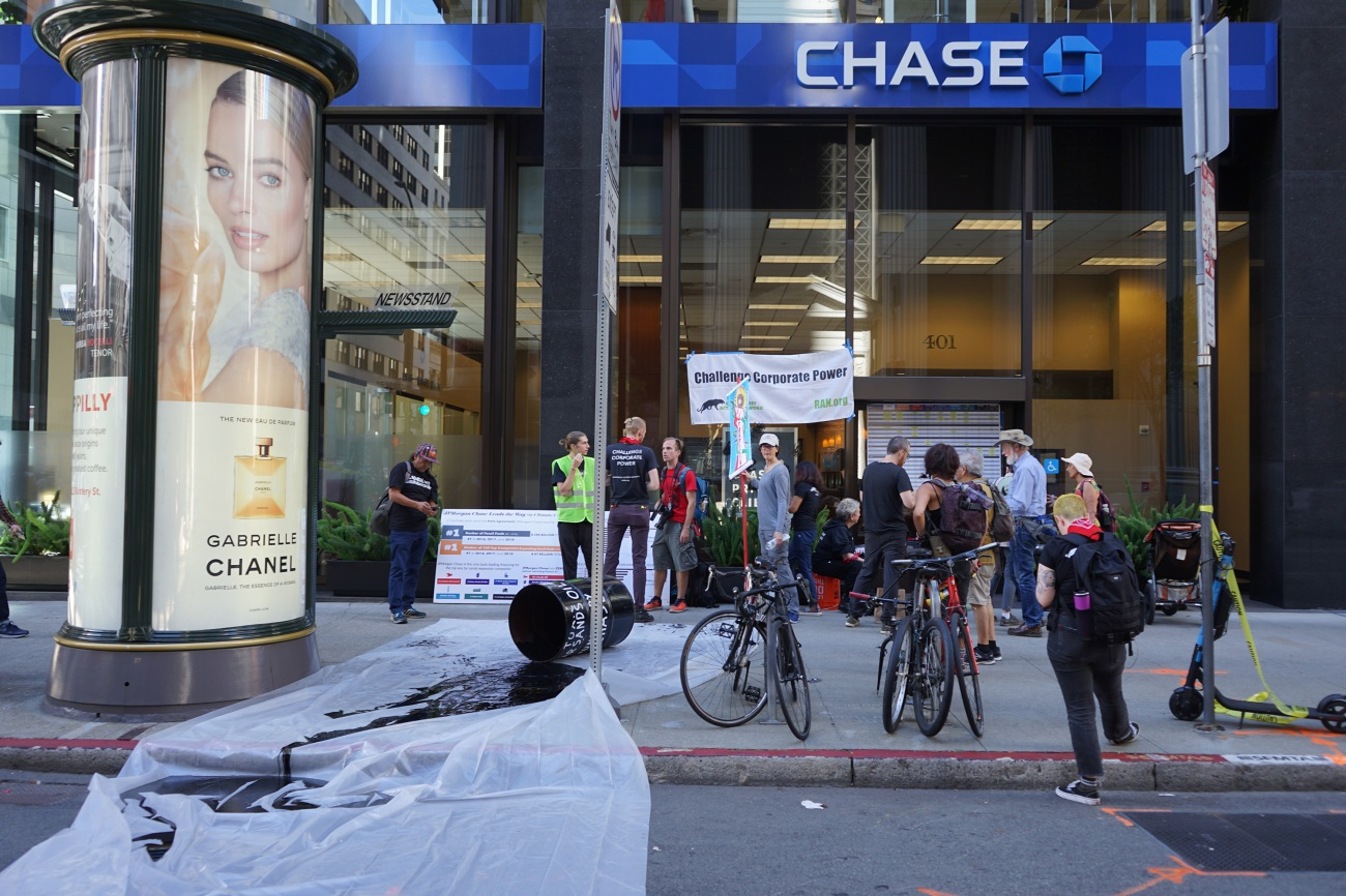A group of activists with the Rainforest Action Network spilled mock oil outside a Chase Bank location.