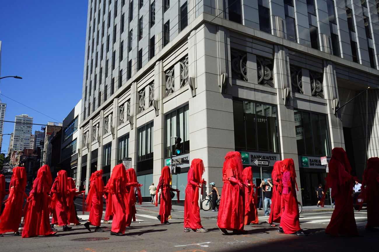 """Calling themselves """"the Red Rebels,"""" a flock of demonstrators in canary red robes moved dramatically slowly through the streets."""