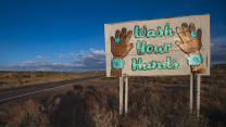 "A sign featuring native Navajo turquoise jewelry reads ""Wash Your Hands"" for passersby on a highway 98 on the Navajo Reservation."