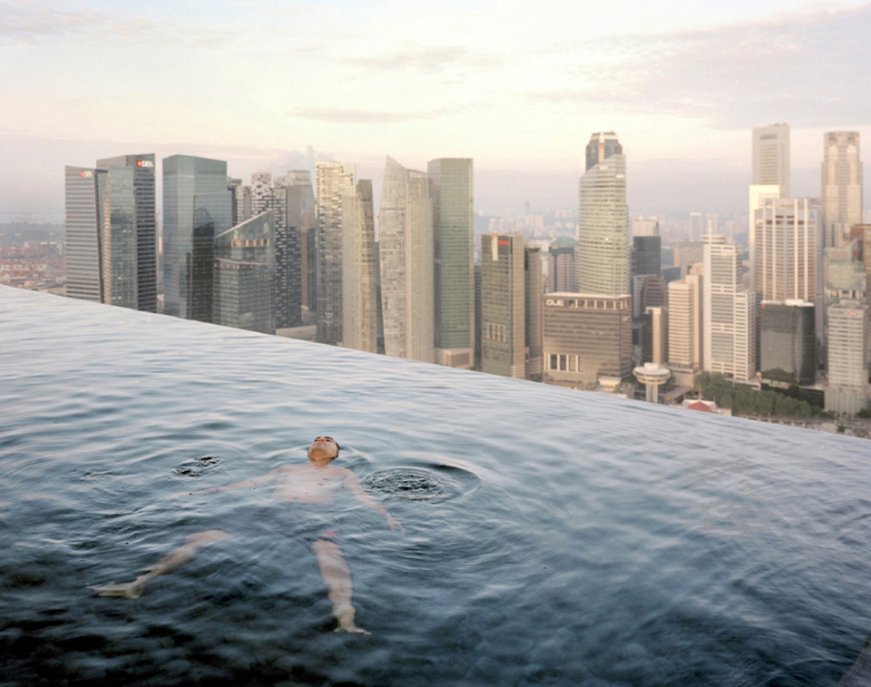 A man floats in the 57th-floor swimming pool of the Marina Bay Sands Hotel, with the skyline of the Singapore financial district behind him.