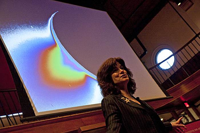 Carolyn Porco lecturing with an image of Saturn's moon Enceladus, giving off a plume, in the background.