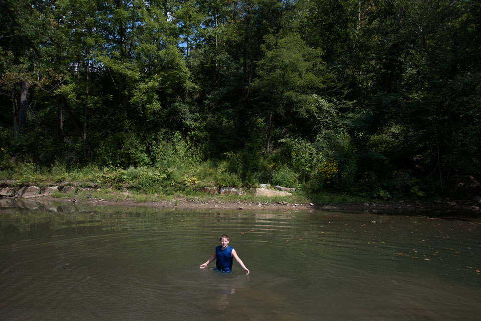 Boy being baptised in river.